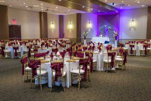 Red Oak Ballroom in Austin, chiavari chairs with ties, plate chargers, stage with head table and arch